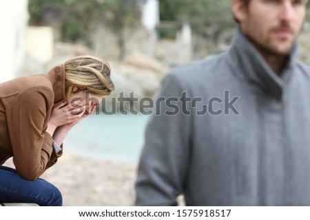 Sad girlfriend complaining after break up sitting on the beach and angry boyfriend leaving her in winter