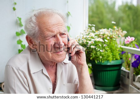 sad, gloomy senior man speaking on the phone with somebody