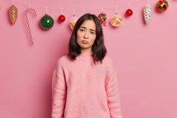 Sad gloomy woman with dark hair wears casual jumper looks unhappily at camera has spoiled mood on Christmas Eve because guests did not come on party isolated over pink background. New Year decoration