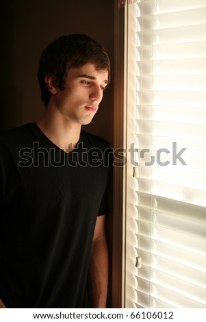 sad handsome young man looking out window