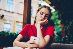 Sad hipster girl browsing boring websites on smartphone during leisure time in coffee shop outdoors.Dispirited female blogger reading repetitious news spending recreation time on social networks