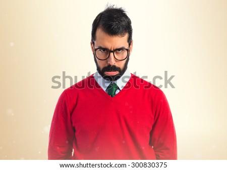 Sad hipster man over ocher background