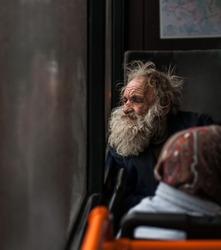 sad homeless old man in public transport near window