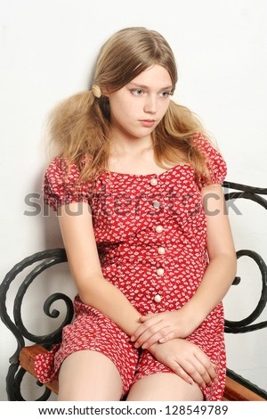 sad innocent teen girl sitting on the iron bench isolated on white