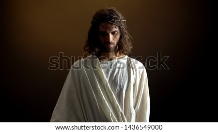 Sad Jesus lowered head in crown of thorns, suffering for mankind sins, expiation
