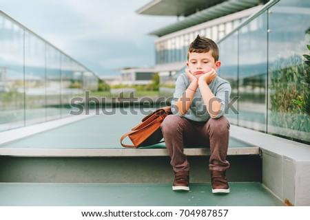 Sad kid boy resting outdoors. Bored little student