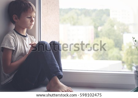 sad kid sitting on window...