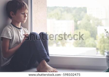 sad kid sitting on window...