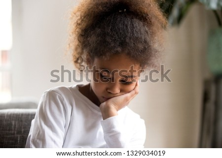 Sad little African American preschool kid feel down or depressed suffer from family problems, upset small mixed race girl child sit alone at home, bored or hurt, offended having troubles with friends