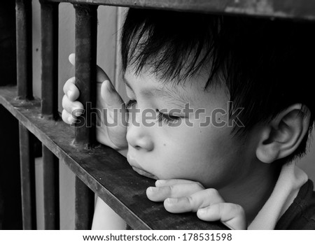 Sad little Asian boy feeling lonely at home,black and white color