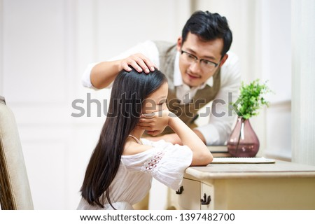 sad little asian girl sitting at desk in her room and getting comfort from caring father #1397482700
