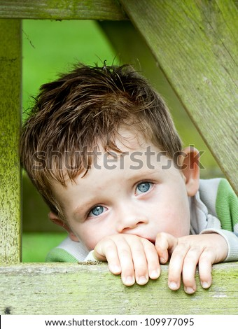 sad little boy inside a wooden frame
