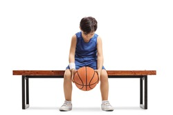 Sad little boy sitting on a bench with a basketball isoalted on white background