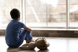 Sad little boy sitting on floor beside window