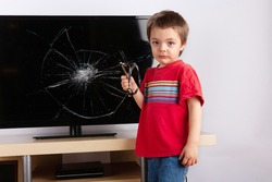 Sad little boy standing in front of a TV with broken screen holding a slingshot. Home insurance concept.