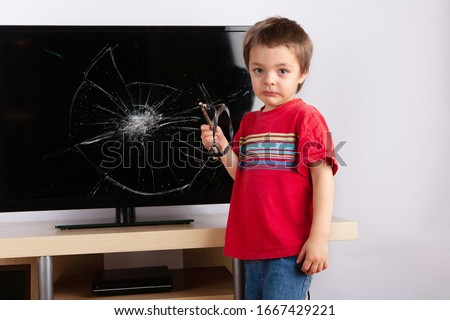 Sad little boy standing in front of a TV with broken screen holding a slingshot. Home insurance concept. Stock photo ©