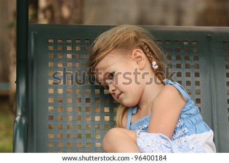sad little child on a bench