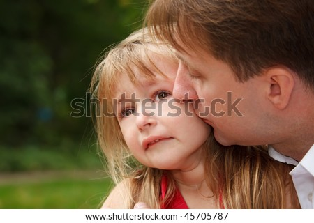 Sad little girl cries in park. Father calms her kissing on cheek.  Close up.