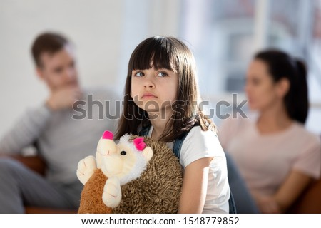Sad little girl feel upset lonely hug fluffy toy hedgehog friend affected by parent fight or quarrel, upset small child loner stressed with mom and dad divorce or split, family problems concept