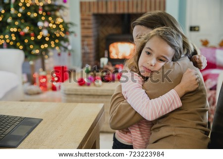 Sad little girl is cuddling with her mother at christmas time.