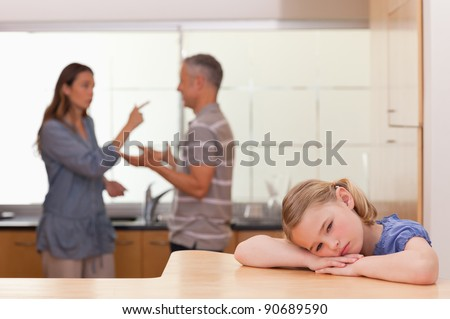 Sad little girl listening her parents having an argument in a kitchen