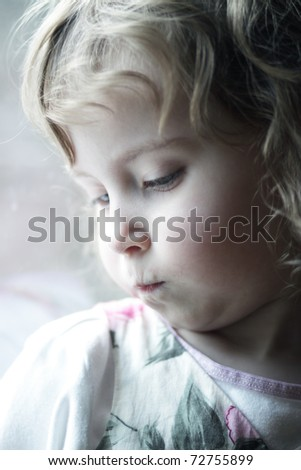 Sad little girl looks out the window