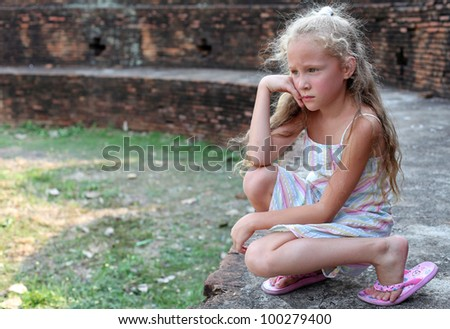 sad little girl on the background of an old brick wall