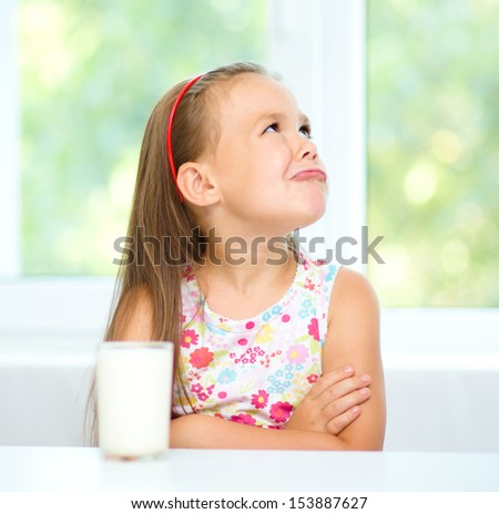 Sad little girl refuses to drink a glass of milk - stock photo
