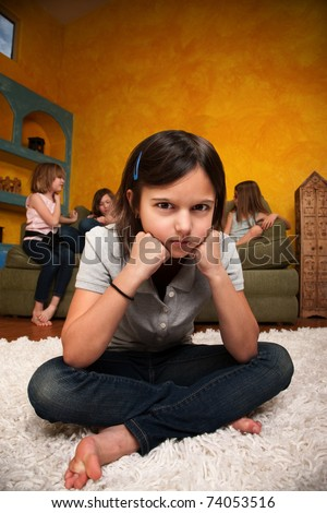 Sad little girl sits away from her friends