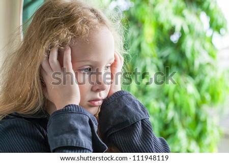 sad little girl sitting near the window