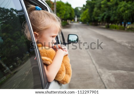 sad little girl sitting near the window in the car with toy in her hands