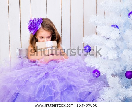 sad little girl with a gift in hands near white Christmas tree