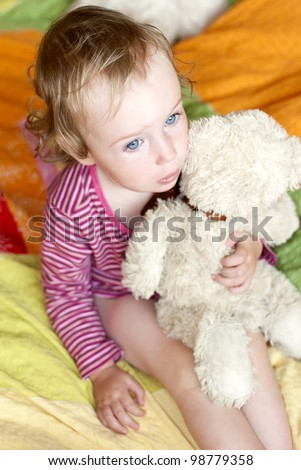 Sad little girl with blue eyes sitting on a bed with a teddy bear.