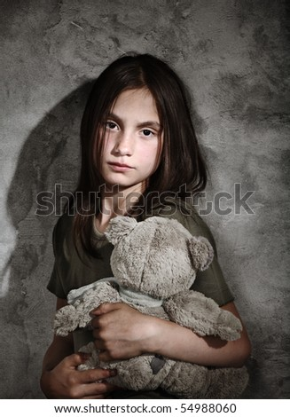 Sad little girl with toy - stock photo