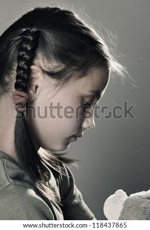 Sad little girl with toy on grey background closeup