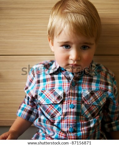 Sad little kid in a checkered shirt. - stock photo