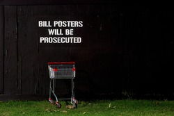Sad little shopping trolley in front of a black wooden wall stenciled with the warning sign that Bill Posters will be Prosecuted.