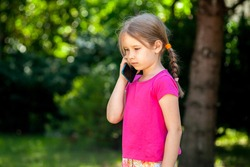Sad lone little school age girl, child talking on the phone, smartphone outside. Unhappy, downhearted kid alone, phone call sad news, loneliness concept. Outdoors lifestyle shot, copy space, closeup