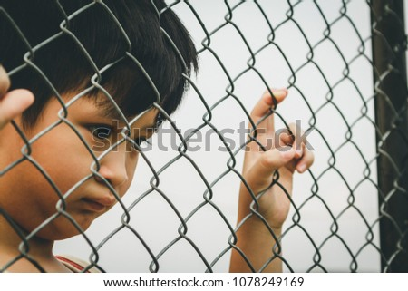 Sad lonely child behind metal wire mesh fence. Concept for child abuse, human trafficking and domestic violence.