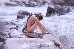 Sad lonely mermaid alien sits on the rocks by the river. Creative costume with a tail and spikes, scales all over the body. Hairstyle long hair with braids. Art photography and processing
