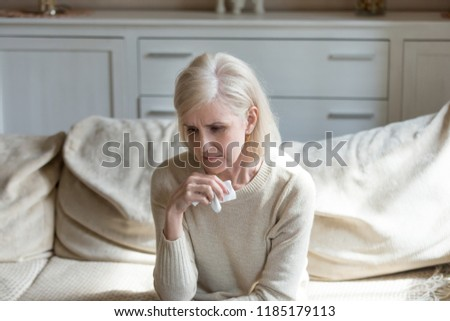 Sad lonely middle aged senior woman crying holding handkerchief feeling depressed at home, thoughtful upset older mature lady mourning grieving concept, thinking of disease, divorce, sorrow or grief