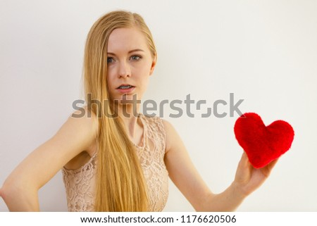 Sad lonely woman being alone holding red heart shape. #1176620506