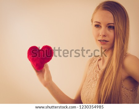 Sad lonely woman being alone holding red heart shape. #1230354985