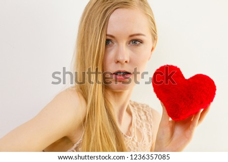 Sad lonely woman being alone holding red heart shape. #1236357085