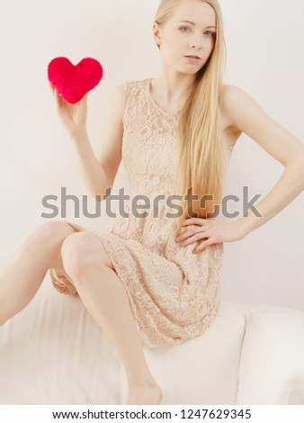 Sad lonely woman being alone holding red heart shape. Female missing someone during valentines. #1247629345