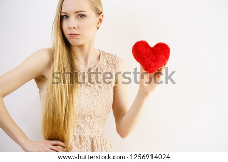 Sad lonely woman being alone holding red heart shape. Female missing someone during valentines. #1256914024