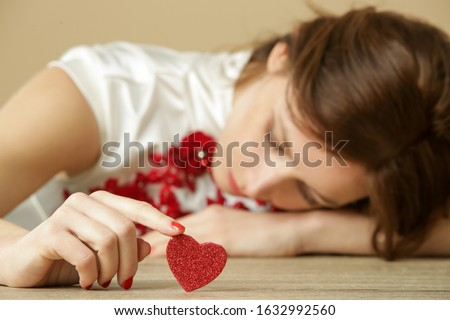 Sad lonely woman holding red heart.  Being alone on Valentine's day. Heartbreak, divorce or breakup concept.