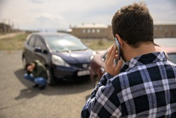Sad man calling roadside service after car crash
