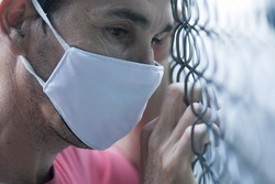 sad man close up wearing face mask holding or leaning on metallic fence looking outside
