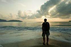 sad man  in the dawn time on the beach